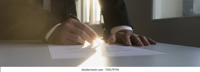 Panorama view of businessman in a shadowy office signing contract or document with a bright light flare from behind.