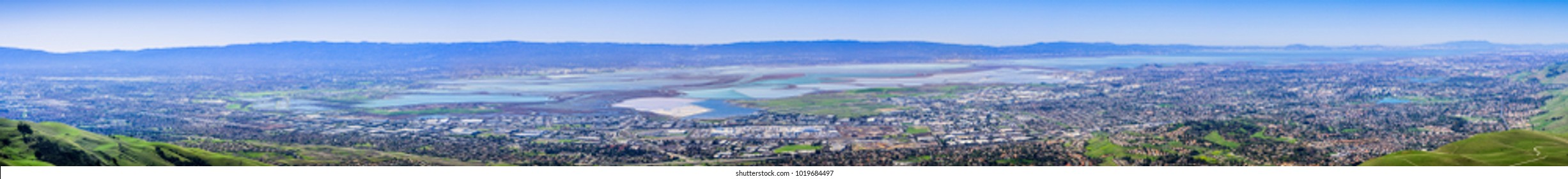Panorama view of the cities on the shoreline of south and east San Francisco bay area; colorful salt ponds in the background; Silicon Valley, California