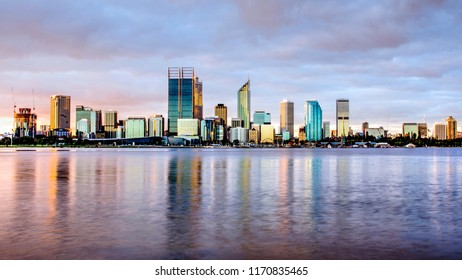 Panorama view of the city of Perth, western Australia, cityscape skyline during golden hour on a cloudy day, with Swan River as foreground