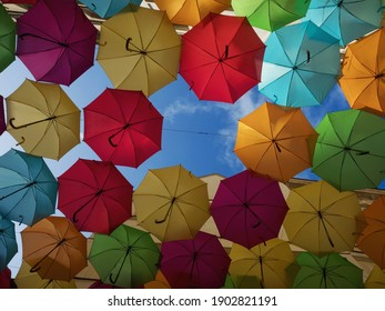 Panorama view of colorful umbrellas sky street decoration art installation in Cite Berryer Le Village Royal Paris France