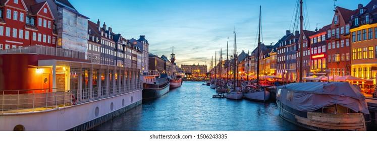 Panorama view of Copenhagen city skyline at night with view of Nyhavn in Copenhagen, Denmark.