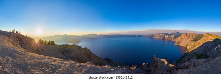 Panorama view of Crater Lake national park at sunset, from the top of the caldera ridge overlooking the water.