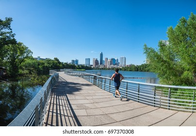 Panorama view Downtown Austin, Texas, US along Colorado River at daytime with cloud blue sky. View from Ann and Roy Butler Hike-and-Bike Trail and boardwalk at Lady Bird Lake, unidentified man running