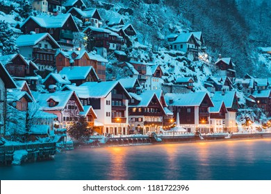 Panorama view of famous Hallstatt lakeside town in the Alps in mystic twilight during blue hour at dawn on a beautiful cold foggy day in winter, Salzkammergut region, Austria