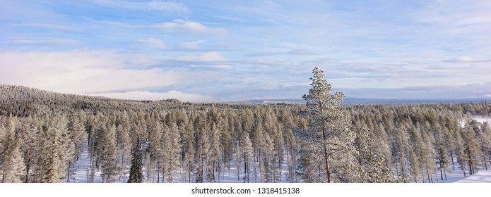 Panorama view of frost covered trees in Idre, Sweden while riding the ski lift to the top of the slope. Valley below with snow covered trees and clouds in the sky during a clear winter day.
