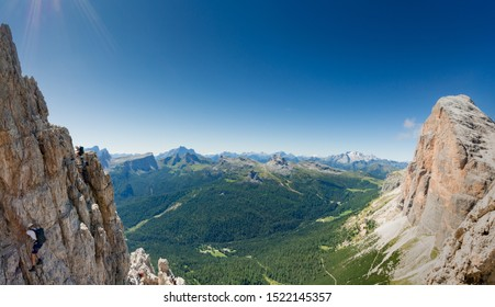 panorama view of a group of climbers on a steep Via Ferrata with a grandiose view of the Italian Dolomites in Alta Badia behind them