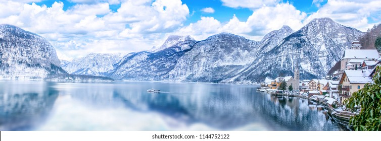 Panorama view of Hallstattersee lake and mountain in daylight with snow. Landscape view of famous Hallstatt lakeside town during winter. Town square in Hallstat. Salzkammergut region, Austria. Europe