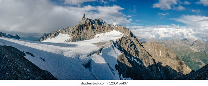 Panorama view of a high alpine mountain landscape of Mont Blanc Massif. Famous alpine peak Dent du Geant and other alpine summits. Glacier, high rock walls and ridges. Chamonix and Courmayer.