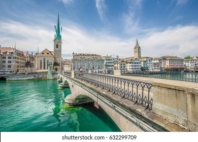 Panorama view of historic city center of Zurich with famous Fraumunster Church and Munsterbucke crossing river Limmat on a beautiful sunny day with blue sky and clouds, Switzerland