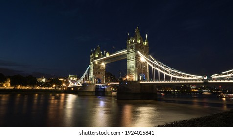 Panorama view of iconic landmark famous illuminated Tower Bridge over Thames river in London England UK Great Britain in Europe at night dark sky