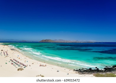 Panorama view of the islands of Lobos and Lanzarote seen from Corralejo Beach (Grandes Playas de Corralejo) on Fuerteventura, Canary Islands, Spain, Europe. Beautiful turquoise water & white sand.