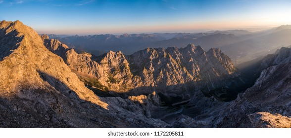 Panorama view from Jubilaumsgrat bivak, between Zugspitze and Alpspitze, Germany/Austria, in the morning with haze in the valley, sunrise from the right