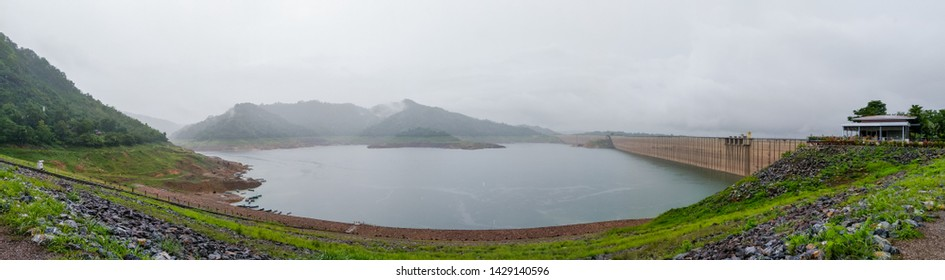 Panorama view of Khun Dan Prakan Chon Dam with rain clouds and mountain in rainy season. Nakhonnayok. Thailand. Asia. Irrigation. Water storage reservoir.