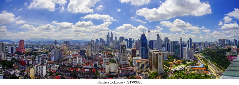 Panorama view of Kuala Lumpur city skyline with dramatic cloud formation and blue sky