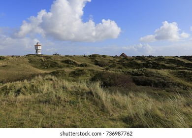 Panorama view of Langeoog. East Frisian island belongs to Lower Saxony in Germany. Dune landscape at blue sky with clouds and the water tower.