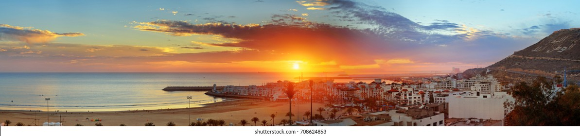 "Panorama view of long, wide beach in Agadir city at sunset, Morocco. The hill bears the inscription in Arabic: ""God, Country, King"""