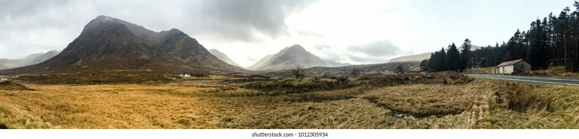 Panorama view of the mountains with grassland and countryside road in the valley of the Scottish highland near Glencoe, Scotland on cloudy day.