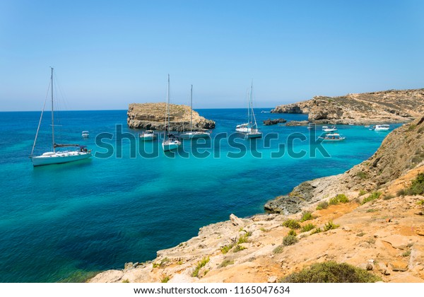 Panorama view on sail boats anchored on open sea in popular bay Blue lagoon on Comino island Malta. Turquoise sea crystal clear and azure ocean, yachts and boats, blue sky without clouds.