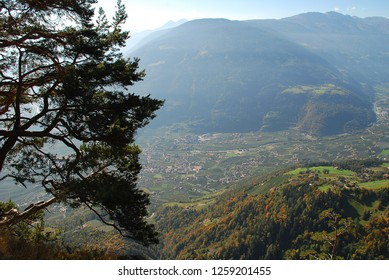 Panorama view on valleys and mountains in the italian alps standing at the Hans-Frieden-Felsenweg (Meran, South Tyrol, Italy). In the valley the village Algund