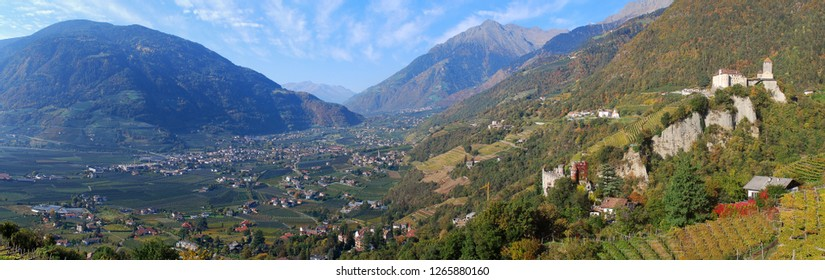Panorama view on valleys and mountains in the italian alps, nearby Meran, South Tyrol, Italy. On the right the Castle Tyrol, in the middle the Brunnenburg castle
