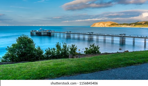A panorama view out to sea in Llandudno, Wales past the Victorian pier as the sun sets on a summers evening