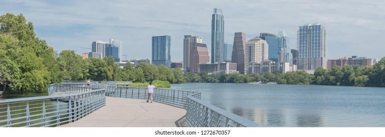 Panorama view people biking running walking along boardwalk near downtown Austin, Texas in summer day