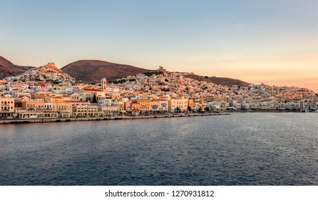 Panorama view of the picturesque townscape of Ermoupoli with port, churches and the chora Ano Syros on the hill at first light, island Syros, Cyclades Aegean Sea, Greece