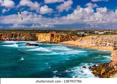Panorama view of Praia do Tonel (Tonel beach) in Cape Sagres, Algarve, Portugal. Seagulls flying over Praia Do Tonel, beach located in Alentejo, Portugal. Ocean waves on Praia Do Tonel beach.