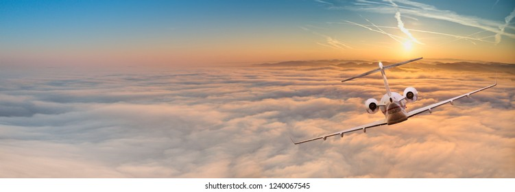 Panorama view of private jet plane flying above dramatic clouds during sunset.
