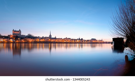 Panorama view of Saumur town from across the Loire river at sunset, with the medieval castle and the old town with Saint-Pierre church.