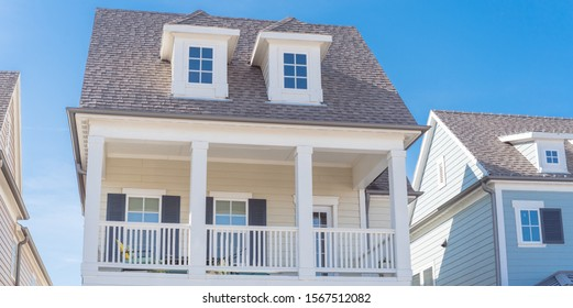Panorama view second story porch with white painted outer edge and banister. Dormer roof windows with weathered shingle siding tiles under cloud blue sky. Country –style houses in suburbs Dallas