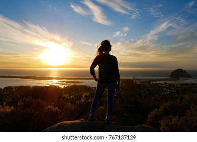 Panorama view of silhouette woman standing on the summit watching Morro Rock sunset , Black hill trail, Morro Bay California