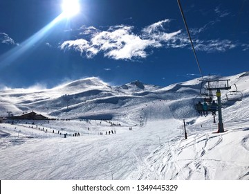 Panorama view of ski resort, slope, people on the ski lift, skiers on the piste among white snow in Valle Nevado near Santiago de Chile. Winter season extreme sports in South America.