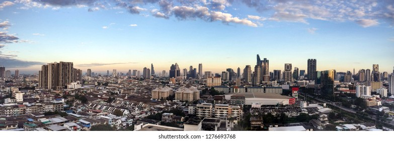 Panorama view of skyscraper in downtown Bangkok, the capital of Thailand in southeast Asia, with white cloud and blue sky at golden sunshine morning.