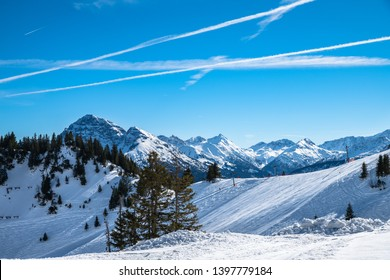 Panorama view of  snow covered Austrian Alps in winter on top of Reutte cable car station, with ski slop in foreground, Tyrol, Austria