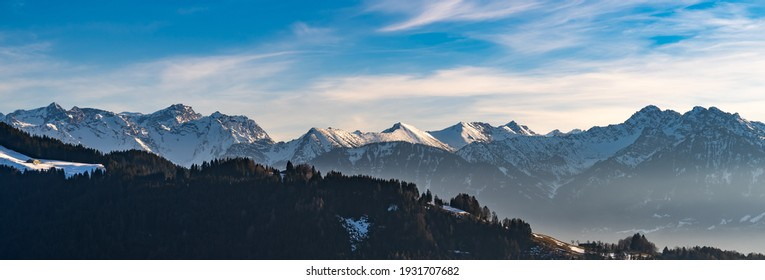 Panorama view of the snowy mountains between Switzerland, Liechtenstein and Austria. in foreground Austrian Alp with meadows and huts in the middle of the woods and in Background mountain range peaks