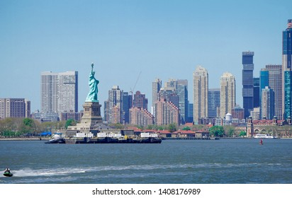 Panorama view of The Statue of Liberty in foreground and New York City skyscrapers in background, Boats in river with blue sky.