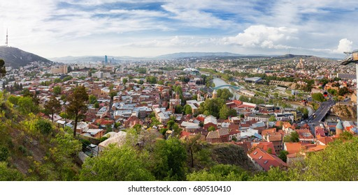 Panorama view of Tbilisi, capital of Georgia country. View from Narikala fortress. Cable road above tiled roofs.