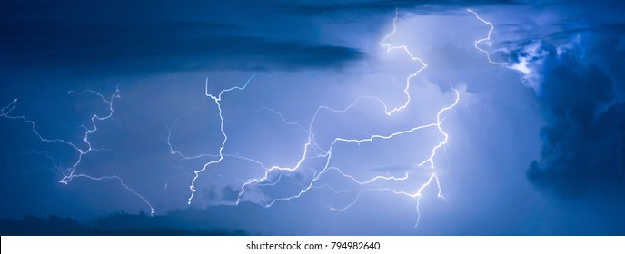 Panorama view of thunder storm lightning strike on the dark cloudy sky background at night.