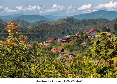 Panorama View of Traditional Akha Hill Tribe Houses on Mountain Top in Nam Ha National Protected Area. Small Ethnic Village in Laotian Rainforest with Mountain Horizon (Luang Namtha, Laos).
