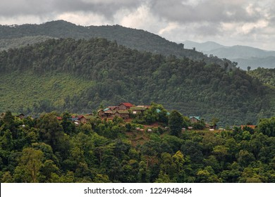 Panorama View of Traditional Akha Hill Tribe Village on Mountain Top Ridge in Nam Ha National Protected Area. Ethnic Village in Laotian Rainforest Surrounded by Green Forest (Luang Namtha, Laos).
