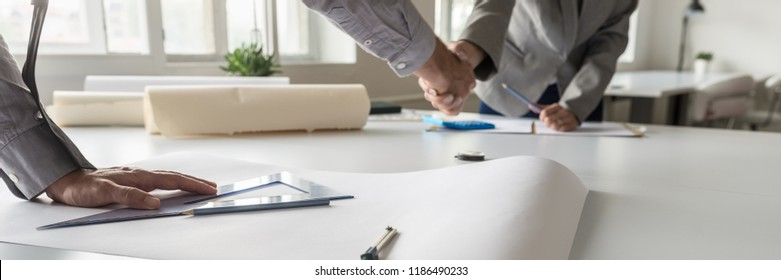 Panorama view of two business partners handshake over sheet of paper on architect table with office supplies.