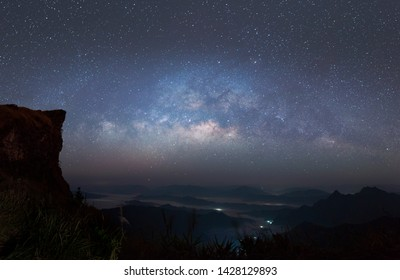Panorama view universe space shot of milky way galaxy with stars on a night sky and mountain in background.