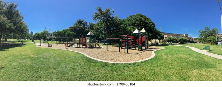 Panorama view urban playground at public park surrounded by large trees and skylines background in downtown Dallas, Texas, USA. Empty recreation place in hot summer day with sunny clear blue sky