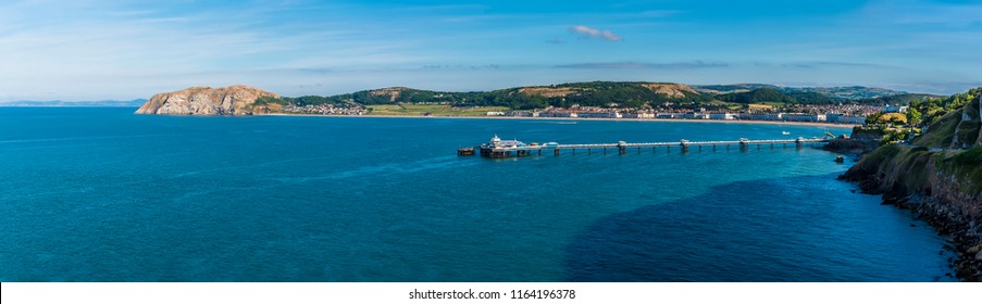 A panorama view of the Victorian pier and shoreline of Llandudno, Wales illuminated by the evening sun in summertime