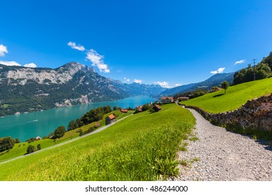 Panorama view Walensee (Walen) lake and the Alps on the hiking trail with green pasture in foreground from south side of the lake, Canton of Glarus, Switzerland.