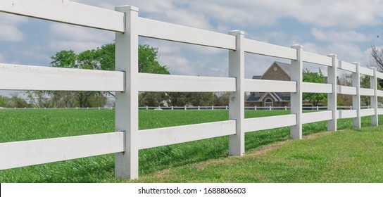 Panorama view wooden white fence with green grass leads to horizontal line under cloud blue sky in countryside of Ennis, Texas, America. Large farmland and ranch protection background.