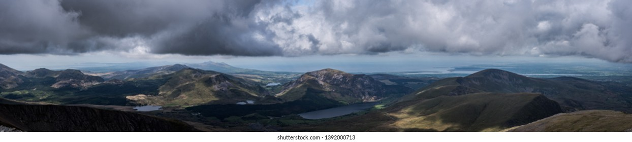 Panorama views across Snowdonia National Park in North Wales, UK. Mountains and coastline, cumulus clouds line the sky, with amazing shades of greens and browns on land. Llyn Peninsula is also visible