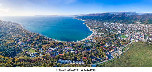 panorama of the village Kabardinka from a bird's eye view. In the foreground of the Kabardinka resort, on the back of the Tsemes Bay and the port of Novorossiysk. On the right  the Markoth Ridge