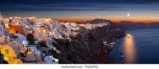 Panorama of the village of Oia on the island of Santorini, Greece, during sunset with full moon